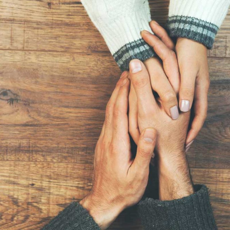 man-woman-holding-hands-wooden-table